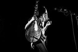 Marie Flore dépasse à peine de sa guitare